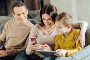 Eltern sitzen zusammen mit Kind auf Sofa