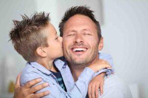 Junge küsst seinem Vater auf die Backe