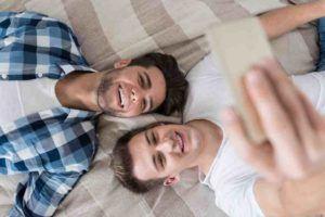 Zwei Männer machen ein Selfie auf dem Bett liegend