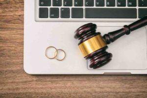 Eheringe und Richterhammer liegen auf einem Laptop