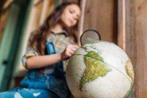 Kind sitzt vor einem Globus