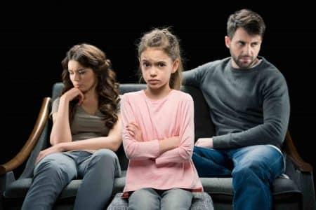 Kind steht vor Eltern mit verschränkten Armen