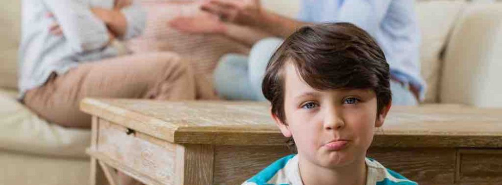Kind sitzt auf dem Fußboden während im Hintergrund die Eltern diskutieren