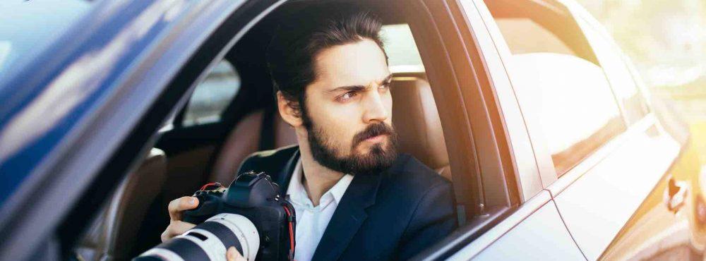Detektiv sitzt mit Kamera im Auto