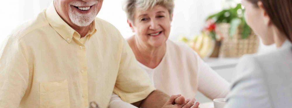Älteres Ehepaar sitzt am Tisch und lächelt, halten Händchen, andere Frau zeigt dem Ehepaar Dokument