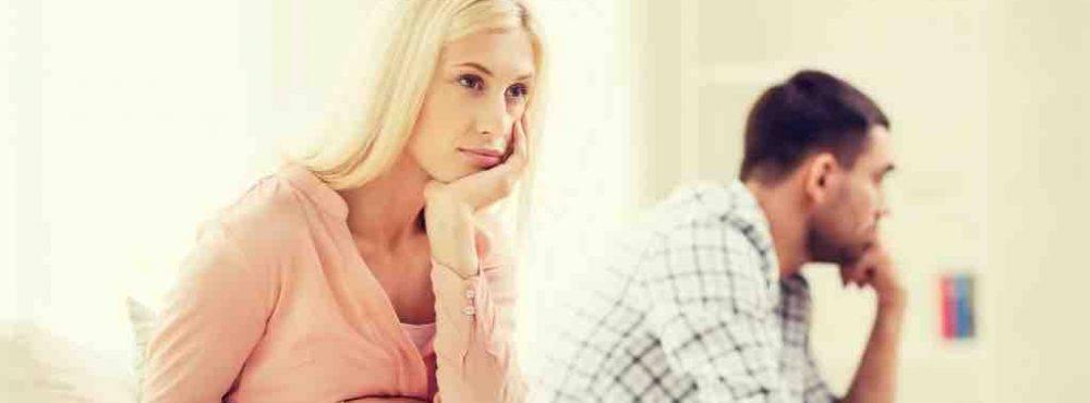 Paar sitzt auf Sofa und schaut in unterschiedliche Richtungen