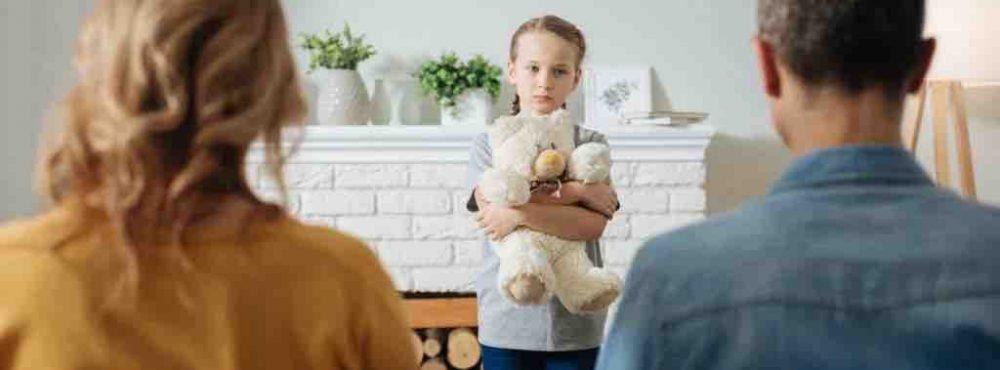 Kind steht vor Eltern mit traurigem Gesicht