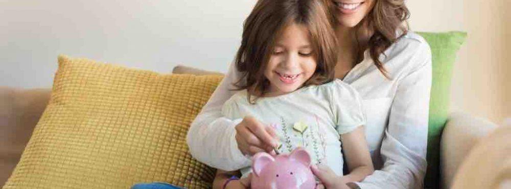Frau sitzt mit Kinde auf Sofa und steckt Geld in ein Sparschwein