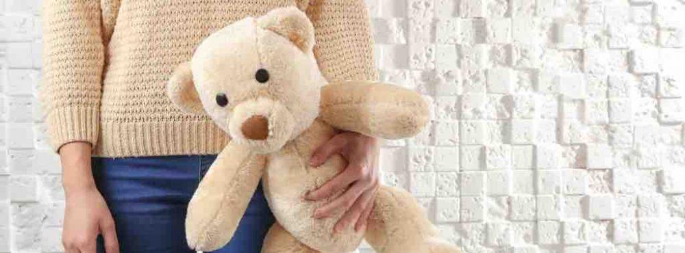 Kind mit Teddybär steht vor einer Wand