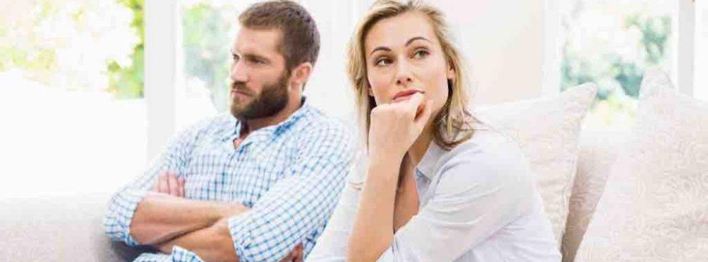 Paar sitzt auf dem Sofa und schaut in verschiedene Richtungen