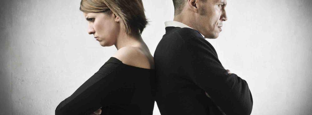 Ein Paar steht Rücken an Rücken und blickt böse