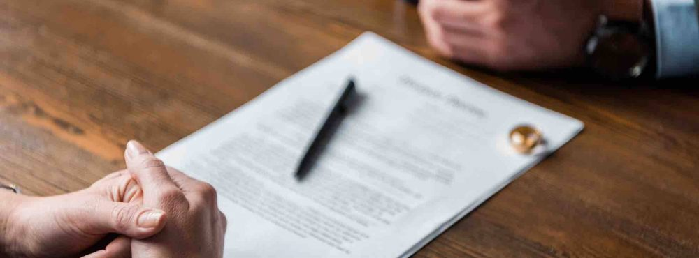 Frauen- und Männerhände, Ehering, Scheidungspapiere