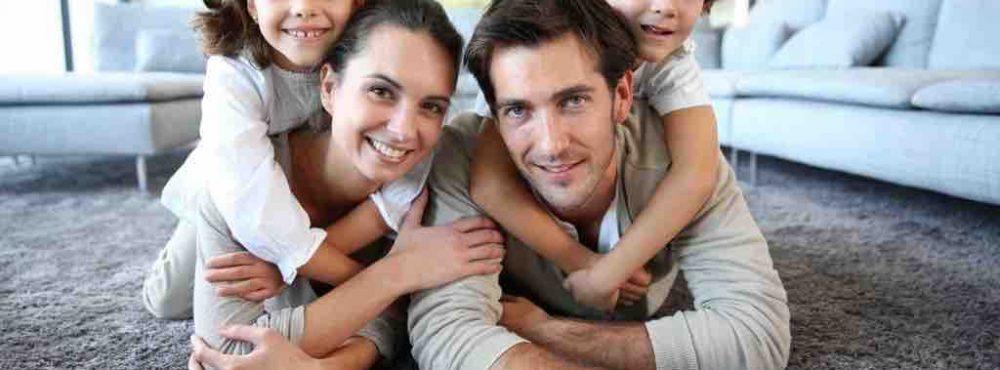 Eltern liegen mit ihren Beiden Kindern auf dem Rücken auf dem Fußboden