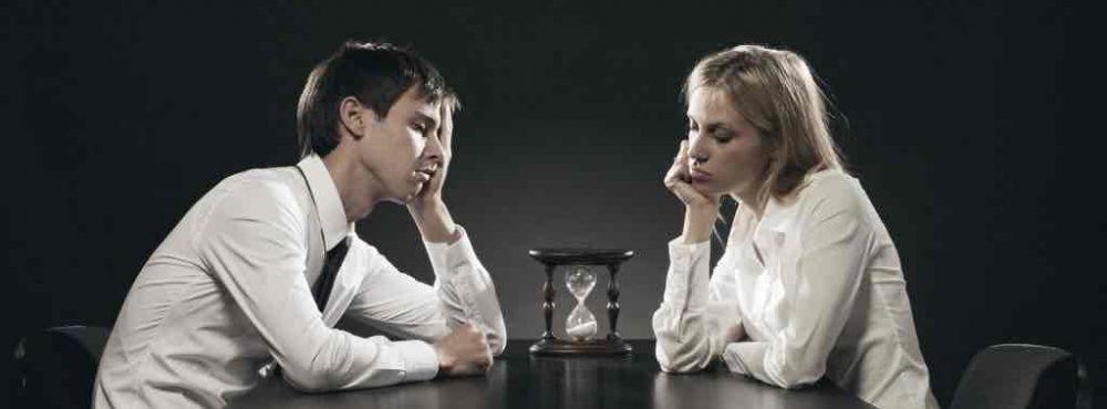 Paar sitzt gelangweilt an einem Tisch vor einer Sanduhr
