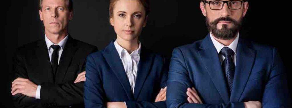 3 Anwälte schauen mit verschränkten Armen in die Kamera