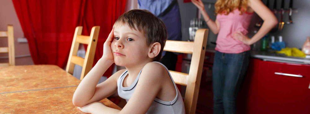 Kind beim Tisch, Eltern im Hintergrund